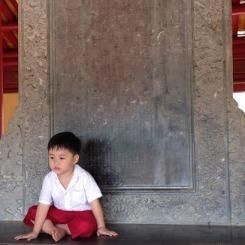 L'enfant assis devant une pierre